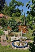 Blaue Pflanzschale mit Steinen und Sukkulenten arrangiert mit verschiedenen Kunstobjekten in sommerlichem Garten