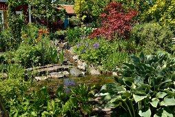 Grünpflanzen um Teich und blühende Blumen in sommerlichem Garten