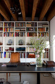 Vase of wildflowers on desk in front of white bookcase in loft apartment with rustic wood-beamed ceiling