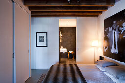Double bed with fur blanket, large, photographic mural and open door leading to ensuite bathroom