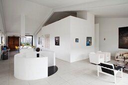 Moderne Loftwohnung, runder Treppenabgang mit weisser Brüstungsmauer, seitlich Loungebereich mit minimalistischem Flair