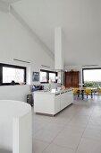 Weisse Kücheninsel und Essplatz in Loftwohnung mit Fliesenboden