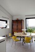 Gelbe Retro Stühle um rundem Tisch, in Ecke antiker Schrank neben raumhohem Fenster