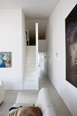 Teilweise sichtbares Sofa in offenem Wohnraum, im Hintergrund Treppenaufgang mit minimalistischem Flair