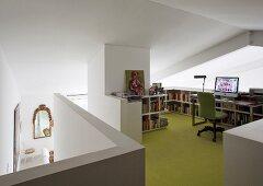 Arbeitsplatz mit halbhohem Regal auf grünem Boden im Galeriebereich
