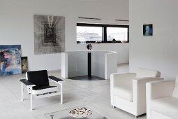 Weisse Designersessel und schwarzer Stuhl in minimalistischem Loungebereich, im Hintergrund Treppenabgang mit kreisförmiger Brüstungswand