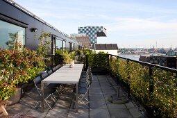 Tischreihe und Klappstühle auf Dachterrasse eines Penthouse, im Hintergrund Stadtsilhouette