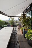 Weisse Markise über Sitzplatz, Tische hintereinander gereiht und graue Klappstühle auf Dachterrasse mit Blumentöpfen auf Boden