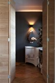 Open double door in wooden wall with view of cot against dark grey wall with sconce lamp