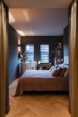 Double bed with scatter cushions and cot in bedroom painted dark grey