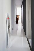 Narrow hallway with white, resin floor and full-length mirror leaning against wall