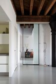 View through floor-to-ceiling, glass sliding door in renovated loft apartment with rustic, wood-beamed ceiling and pale grey resin floor