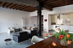 Lounge area in renovated loft apartment with black, industrial column and rustic, wood-beamed ceiling