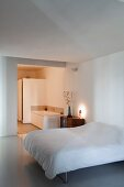 Bedroom with double bed, elegant sideboard and view into ensuite bathroom