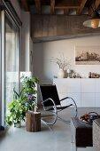 Loftwohnung mit weisem Sideboard, Schaukelstuhl und Grünpflanzen