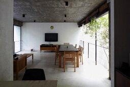 Blick auf Esstisch in offenem Wohnbereich mit Betondecke