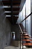 Treppenaufgang aus transparenter Stahlkonstruktion mit Holzstufen, seitlich eine Glasfassade