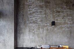 Beschriftete Betonwand hinter Schreibtisch