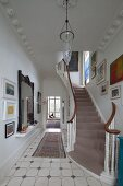 Traditional foyer with Art Nouveau, stucco ceiling, tiled floor and curved staircase with grey runner