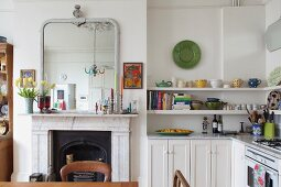 Open fireplace below framed mirror in country-house kitchen with white cupboards