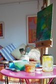 Pots of paint on pink side table and picture on easel