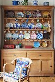 Decorative plates on pale, wooden dresser behind wicker chair with patterned cushions