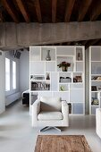 Modern, pale beige armchair in front of white designer shelves with open-fronted and closed modules used as partition in loft apartment