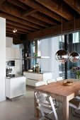 Dining area below mirrored, spherical lamps an open-plan kitchen in child-friendly loft apartment