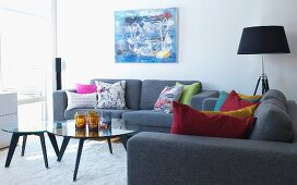 Grey sofa set with colourful scatter cushions around set of glass of coffee table in modern living room