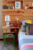 Double bed with striped bedspread, colourful scatter cushions and wooden headboard panel with youthful ornaments on integrated shelves and bedside table