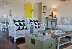 Vintage-style seating area with graphic-patterned scatter cushions on wicker armchairs, coffee table and old wooden trunk in front of yellow door