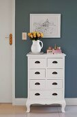 Jug of roses on white, country-house-style chest of drawers below picture on grey-painted wall