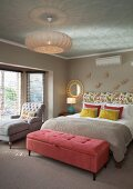 Samtrosa Kleiderbank vor Doppelbett mit Dekokissen und floral gemustertem Kopfteil, Ruhesessel vor Fenster