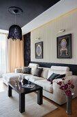 Hängeleuchte über heller Sofalandschaft in elegantem Wohnzimmer mit abgehängter Decke