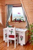 Kleiner Schreibtisch und Stuhl mit Blumenmotiven bemalt am Fenster, in Dachzimmer mit holzverschalten Wänden