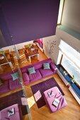 Blick von Galerie auf pinkfarbenes Sofa und Polsterhocker als Tisch, auf diagonal verlegtem Parkettboden in zeitgenössischem Wohnhaus