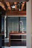 Detail of sink in counter in front of floor-to-ceiling windows with closed louver blinds below wood-beamed ceiling