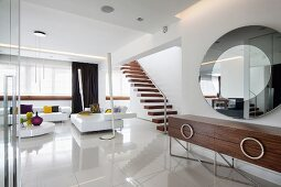 Elegant, loft-style interior - designer sideboard below round mirror on wall, white lounge area and glossy floor