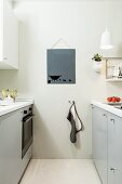 Two opposite, pale grey kitchen counters, tea towel hung on hook and picture on wall