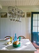 Crockery on table below pendant lamp decorated with cutlery in rustic dining room with wooden walls and ceiling painted white