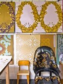 Child's chair and armchair with gilt ornamentation against wallpaper designs on wall of studio
