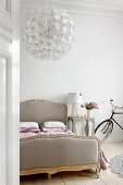 Double bed, designer lamp on bedside table and bicycle