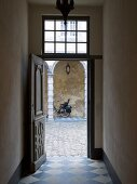 Open, historical front door with diamond-chequered floor tiles and view into cobbled courtyard