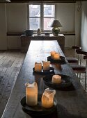 Burning candles on metal trays on a long wooden table with a table under a window in the background in a rustic, historic setting