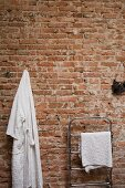 Dressing gown hung on brick wall next to chrome towel rail