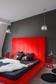 Dramatisch gestaltetes Schlafzimmer, Tierfell und Matratze auf Bodenpolster mit hohem Kopfteil in Rot an dunkelgrauer Wand