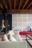 Sitzbereich mit Sofa und Messingleuchten in Loft mit gusseisernen Stützen und Holzbalkendecke; rotes Lowboard vor Raumteiler Kassettenwand