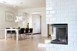 White dining table and black, upholstered chairs in modern, open-plan interior with corner fireplace in white-tiled wall