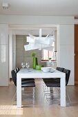Designer lamp above white dining table and black chairs in open-plan interior