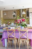 Vase of flowers on table with colourful tablecloth and old wooden chairs in modern kitchen with row of pendant lamps above counter